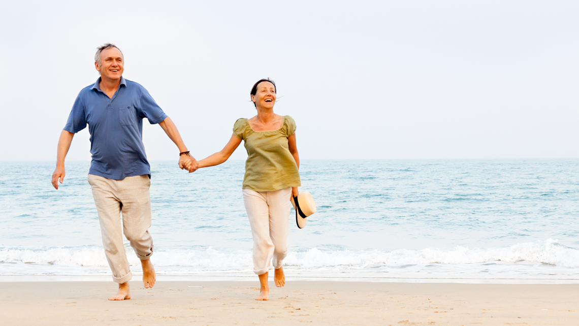 Retired senior couple walking on the beach